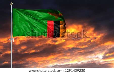 flag of Zambia on flagpole fluttering in the wind against a colorful sunset sky #1291439230