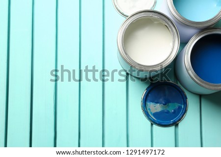Colorful paint cans on blue wooden background, top view. Space for text #1291497172