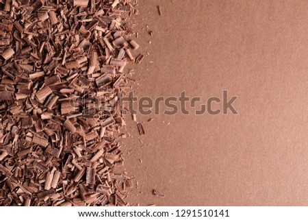 Chocolate curls and space for text on color background, top view #1291510141