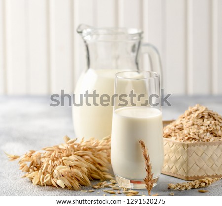The concept of a vegetarian diet. Oat milk in the glass with jug of oat milk and oat and oat ears. Light background #1291520275