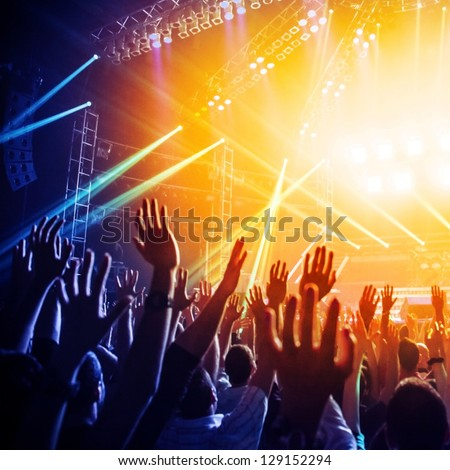 Photo of many people enjoying rock concert, crowd with raised up hands dancing in nightclub, audience applauding to musician band, night entertainment, music festival, happy youth, luxury party Royalty-Free Stock Photo #129152294