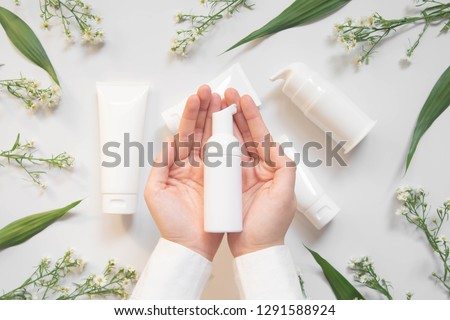 Beauty natural skincare products development concept. Dermatologist hands holding blank cosmetic skincare bottle w/ pump dispenser and organic ingredient on white background. Top view. Close up. #1291588924