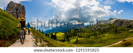 Couple cycling in Cortina d'Ampezzo, stunning Cinque Torri and Tofana in background. Woman and man riding MTB trail. South Tyrol province of Italy, Dolomites. #1291591825