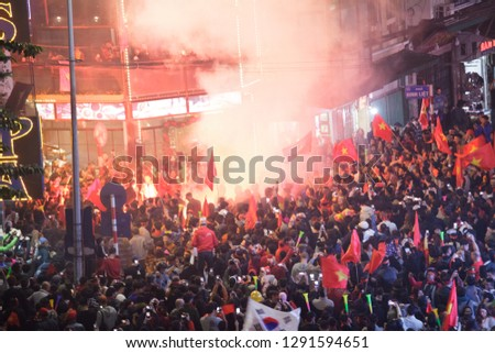 Crowd of Vietnamese football fans down the street to celebrate the win after Vietnam team won in AFF Cup 2018, with a lot of Vietnamese flags raising high. #1291594651
