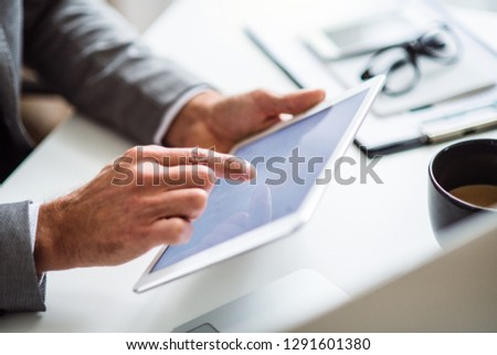 A midsection of businessman sitting at the table, using tablet. Copy space. #1291601380