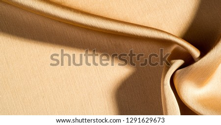 Background, pattern, texture, beige golden silk fabric It has a smooth matte finish and is durable due to a slightly twisted yarn. #1291629673