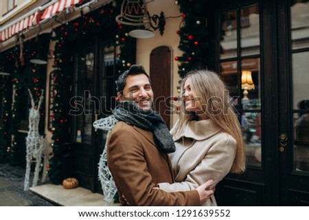 Lovely couple laughing and have fun outside on christmas decoration background #1291639552