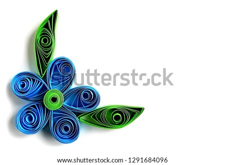 Origami blue flower & paper green leaves frame in quilling technique. Beautiful origami paper flower with leaves - quilling art element. Handmade kids quilling origami flower & leaves from color paper #1291684096