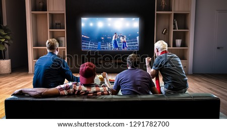 Group of fans are watching a boxing moment on the TV and celebrating a knockout, sitting on the couch in the living room. The living room is made in 3D. #1291782700