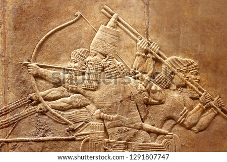 Assyrian relief on the wall. Ancient carving on the stone from Middle East history close-up. Remains of the culture of ancient civilization. Assyrian and Sumerian art for vintage background. #1291807747