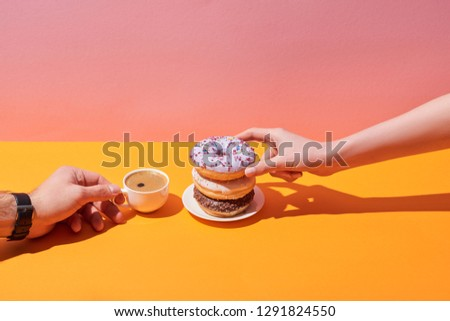 cropped view of woman and man taking tasty donuts on saucer and coffee cup on yellow desk and pink background #1291824550