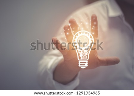 Business idea and vision, businessman holding light bulb, concept of new ideas, innovation, invention and creativity, retro toned image, selective focus. #1291934965