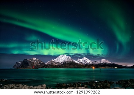 Visiting the Lofoten Islands during winter time is a dream for all landscape photographers. At this time of the year, the colourful and enchanting Aurora Borealis light up the clear night skies above #1291999282