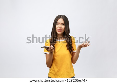 Portrait of a furious asian woman talking on mobile phone isolated over white background #1292056747
