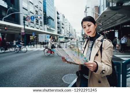 Discovering new places in kyoto japan spring vacation. beautiful young woman holding map and looking while standing on busy city street. local japanese people riding bike bicycle background. #1292291245