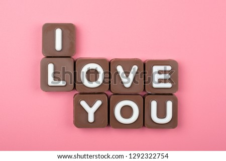 I love you engraved in chocolate on colored background