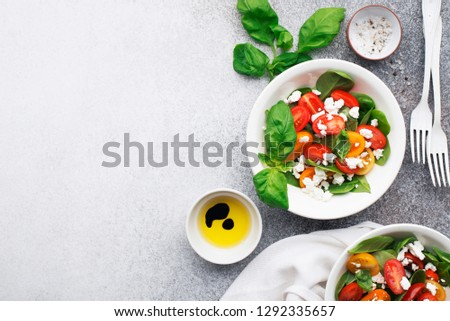 Healthy food. Salad of colored cherry tomatoes, cottage cheese, basil with olive oil, balsamic, sea salt, portioned black pepper. top view. On a gray dark background. #1292335657