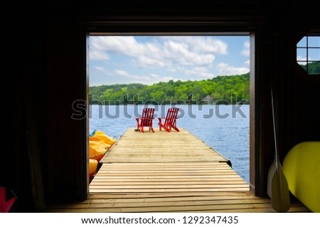 View of two red Adirondack chair on a wooden dock from a cottage's boathouse in Muskoka, Ontario Canada. In the background cottages are nestled between trees. #1292347435