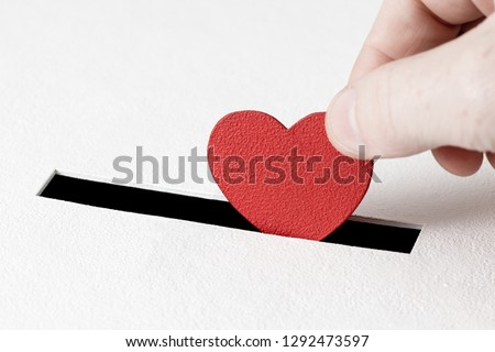 Red heart symbol is put by person's hand into slot of white donation box. Concept of sincere devotion to faith. Concept of donorship, life saving or charity. Close-up shot #1292473597