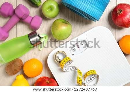 Flat lay composition with scales, healthy food and sport equipment on wooden background. Weight loss #1292487769