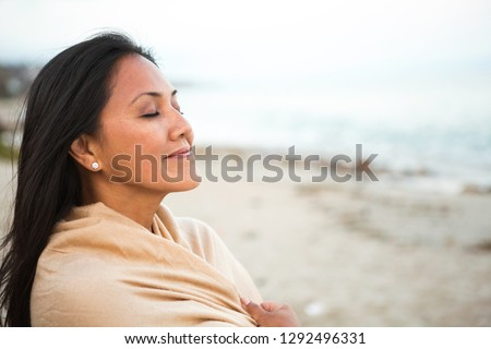 Beautiful confident Asian woman standing on the beach. Royalty-Free Stock Photo #1292496331