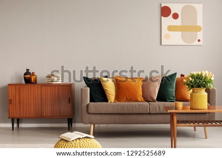 Books and vases on retro cabinet next to comfortable sofa with pillows #1292525689