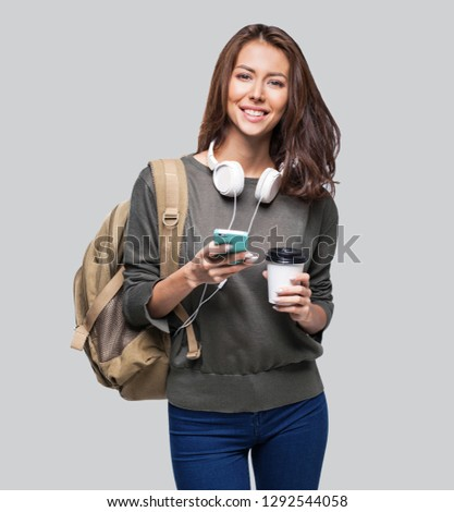 Portrait of young beautiful woman with smart phone and coffee. Smiling student girl going on travel. Studio shot isolated on gray background. Travel, student lifestyle, technology, connection concept #1292544058