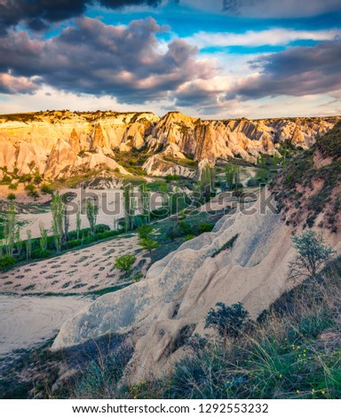 Colorful summer sunset in Cappadocia. Picturesque evening view of Red Rose valley. Cavusin village located, district of Nevsehir Province in the Central Anatolia Region of Turkey, Asia. #1292553232