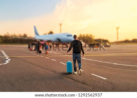 Man tourist passager getting in to airplane at airport, walking from the terminal to the plane. #1292562937