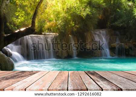 wooden table with Waterfall in spring season background