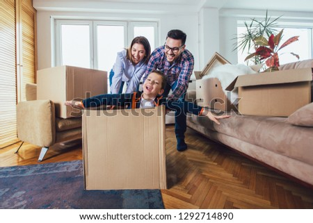 Happy family moving home with boxes around, and having fun. #1292714890