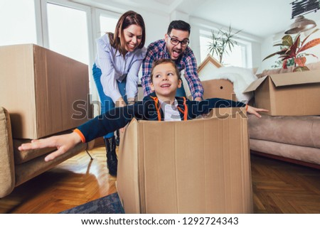 Happy family moving home with boxes around, and having fun. #1292724343