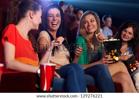 Happy girls sitting in multiplex movie theater, talking, laughing.