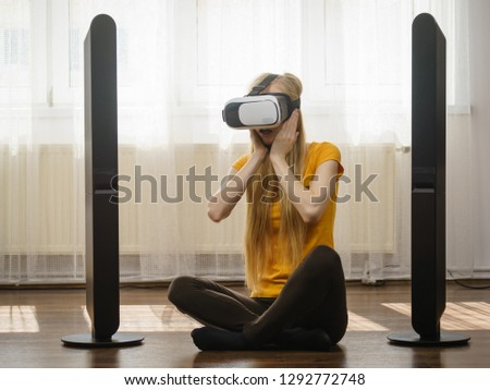 Young woman wearing virtual reality goggles vr 3d box sitting on floor in living room, listening to music. Connection, technology, new generation and progress concept. #1292772748