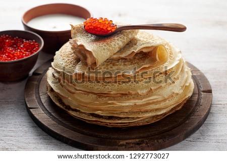 Stack of russian thin pancakes blini with red caviar and fresh sour cream. Shrovetide Maslenitsa festival meal on white wooden background. Rustic style, close up view Royalty-Free Stock Photo #1292773027