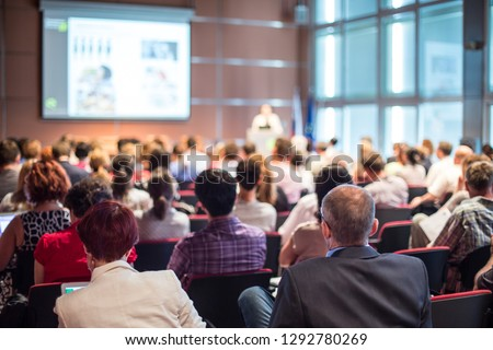 Speaker giving a talk in conference hall at business event. Audience at the conference hall. Business and Entrepreneurship concept. Focus on unrecognizable people in audience. Royalty-Free Stock Photo #1292780269