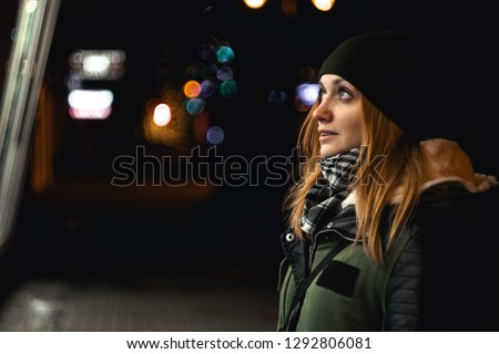 Outdoor night photo of young happy smiling girl looking through shop window, city lights on background, in street of european city, wearing knitted olive hat, scarf #1292806081
