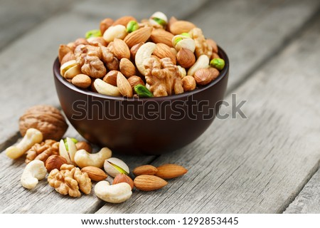 Wooden bowl with mixed nuts on a wooden gray background. Walnut, pistachios, almonds, hazelnuts and cashews, walnut. #1292853445