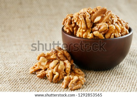 Peeled walnuts in a wooden, dark brown cup on a burlap cloth. #1292853565