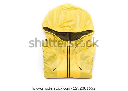 Folded yellow zipper windbreaker jacket, rain proof jacket hoodie. Track jacket sport shiny nylon full zip isolated on white. Folded clothes. #1292881552