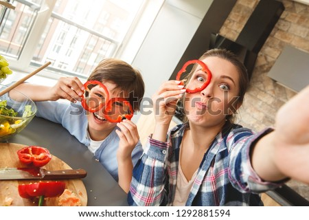 Mother and son at home standing in kitchen together taking selfie photos on smartphone looking camera grimacing covering face with bell pepper circles silly