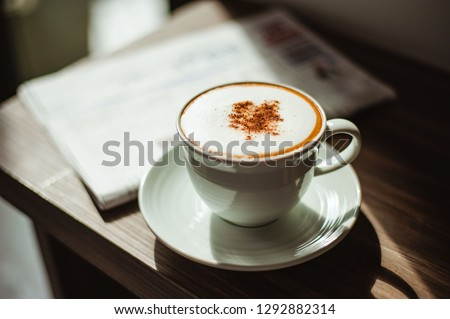 Two cups of cappuccino with latte art on wooden background and newspaper. Cup of cappuccino with newspaper on the table.Coffee Shop Cafe Latte Cappuccino Newspaper Concept  #1292882314