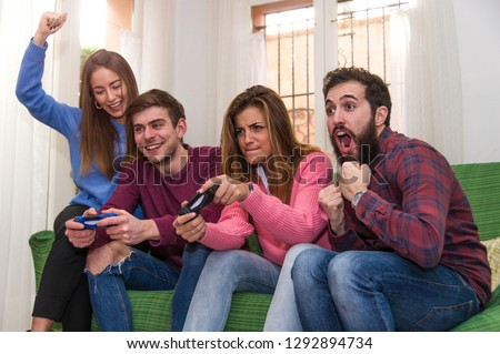 Group of friends having fun playing videogames sitting on the sofa at home. Concept about technology, videogames, lifestyle and people #1292894734