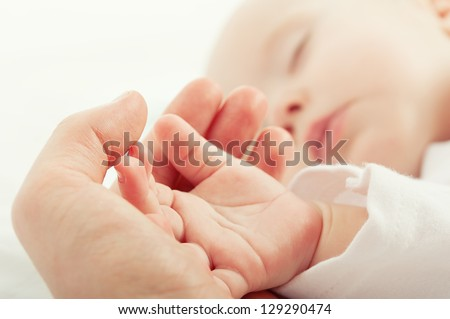 hand the sleeping baby in the hand of mother  close-up Royalty-Free Stock Photo #129290474