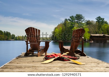 Two Adirondack chairs on a wooden dock facing the blue water of a lake in Muskoka, Ontario Canada. Canoe paddles and life jackets are on the dock. A cottage nestled between green trees is visible. #1292940571