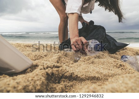 Volunteer woman collecting trash on the beach. Trash-free seas concept. Single-use plastic is a human addiction that is destroying our planet #1292946832