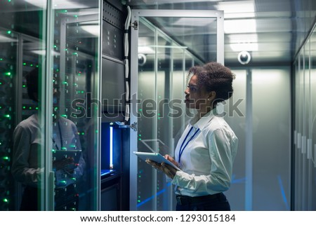 Medium shot of female technician working on a tablet in a data center full of rack servers running diagnostics and maintenance on the system #1293015184