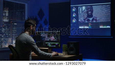Medium shot of a young man sitting back and editing video inside a room