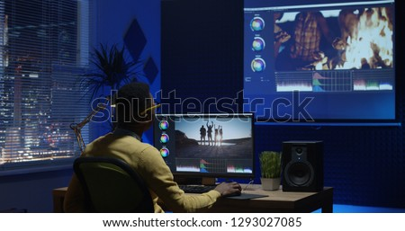 Medium shot of a young man editing video inside the modern video studio while his colleagues are giving instructions