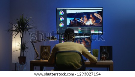 Medium shot of a young man sitting back and editing a video inside a modern video studio Royalty-Free Stock Photo #1293027154